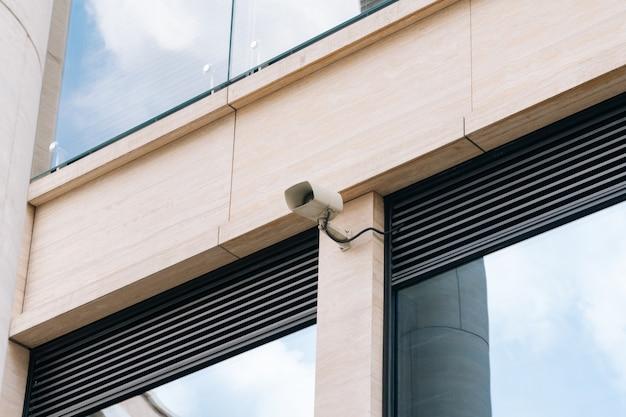 Uma câmera de cftv ao ar livre na parede de um escritório de negócios. o conceito de proteger as empresas do hooliganismo Foto Premium