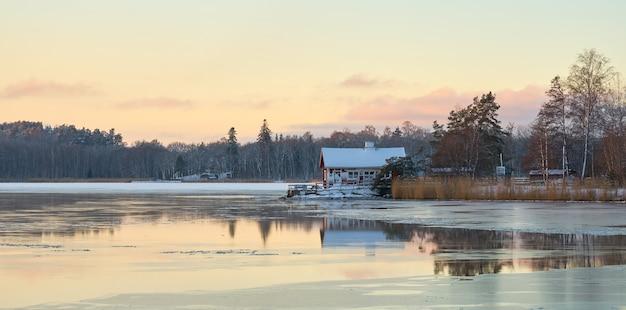 Uma casa nas margens do congelante mar báltico ao pôr do sol. Foto Premium