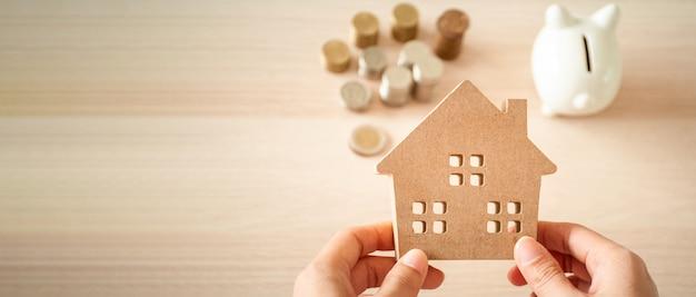Uma casa realizada nas mãos de uma mulher planejando economizar dinheiro para investir em imóveis. para economizar ou investir em uma casa. Foto Premium