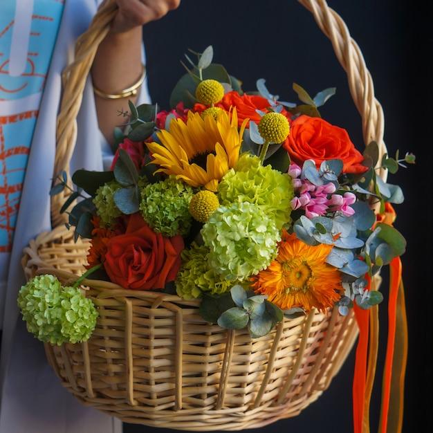 Uma cesta de bambu de girassóis, rosas vermelhas e cravos Foto gratuita