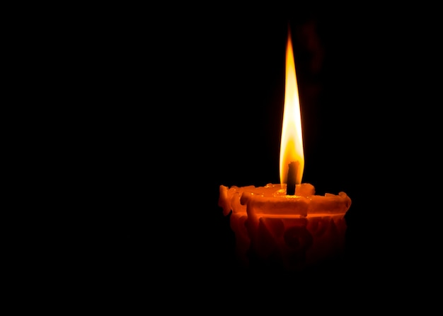 Uma chama de uma vela no fundo da noite escura Foto Premium