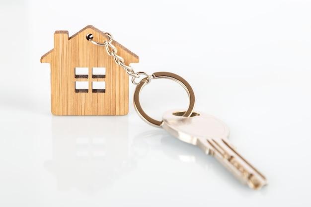 Uma chave em uma casa em forma de chaveiro de madeira Foto Premium