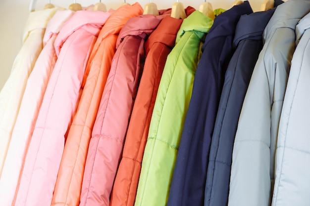 Uma coleção de elegantes casacos de outono em cabides na loja Foto Premium