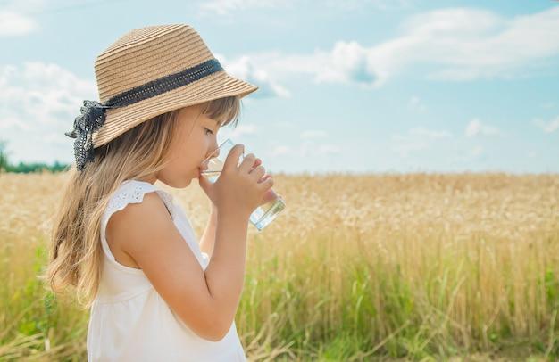 Uma criança bebe água no fundo do campo Foto Premium