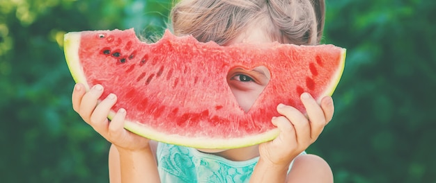 Uma criança come melancia. foco seletivo. comida. Foto Premium