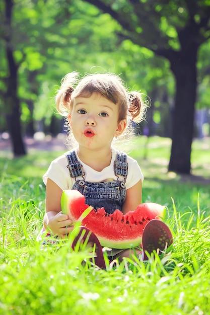 Uma criança come melancia. foco seletivo. Foto Premium