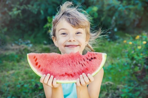Uma criança come melancia. Foto Premium