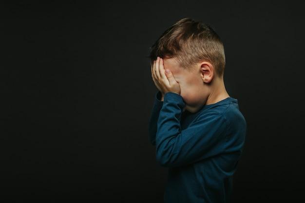 Uma criança cuja depressão com as mãos fechadas Foto Premium
