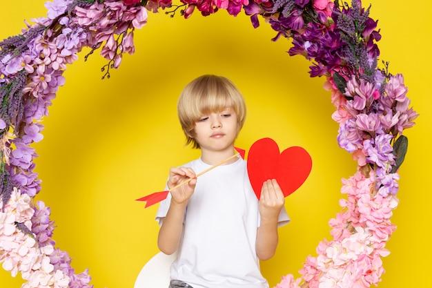 Uma criança de blodne vista frontal em t-shirt branca segurando coração forma sentado sobre a flor fez ficar no espaço amarelo Foto gratuita