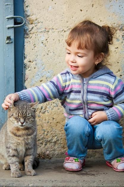 Uma criança e um gato. foco seletivo. Foto Premium