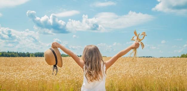 Uma criança em um campo de trigo. Foto Premium