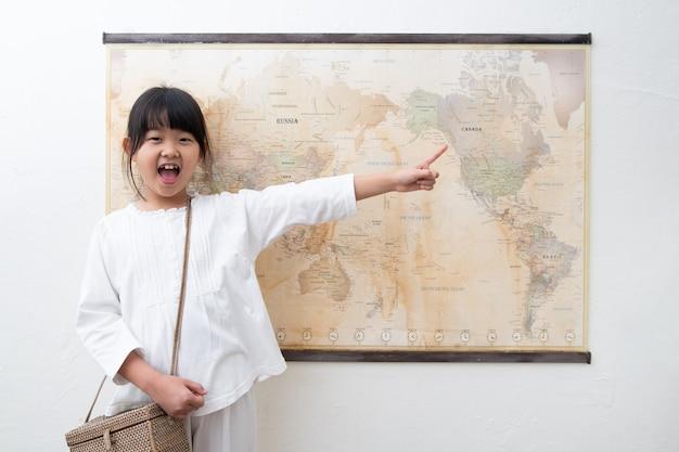 Uma criança está apontando e rindo do mapa do mundo. Foto Premium