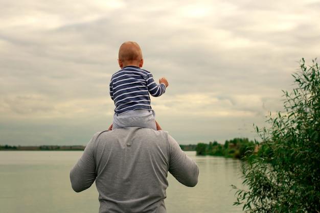 Uma criança no pescoço do pai. ande perto da água. bebê e pai contra o céu. Foto Premium