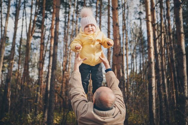 Uma criança pequena com o pai em um terno quente caminha na floresta. parque de outono. o conceito de moda infantil, acessórios, caminhadas ao ar livre Foto Premium