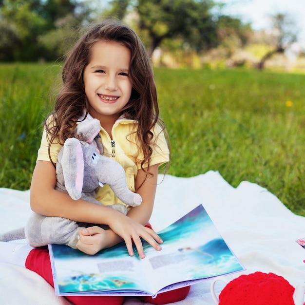 Uma criança pequena está lendo um livro e sorrindo. quadrado. o conceito Foto Premium