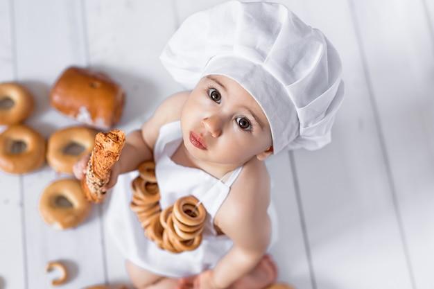 Uma criança vestida, o chef come um coque Foto Premium