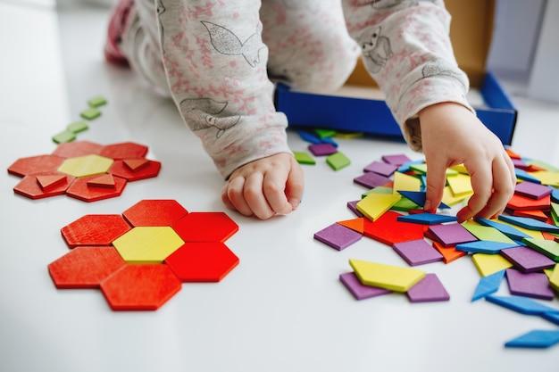 Uma criancinha brinca com quebra-cabeça ou tangram, educação Foto Premium