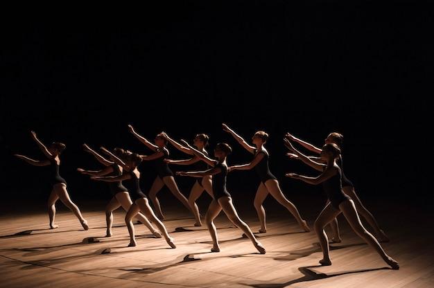 Uma dança coreografada de um grupo de graciosas jovens bailarinas praticando no palco de uma escola de balé clássico Foto Premium