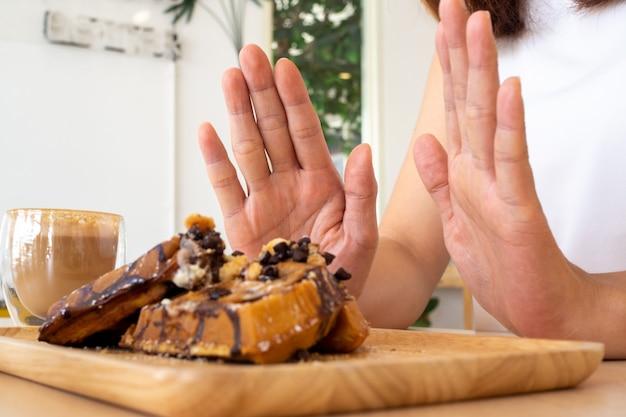 Uma das meninas da assistência médica usou a mão para empurrar um prato de bolo de chocolate. recuse-se a comer alimentos que contenham gordura trans. Foto Premium