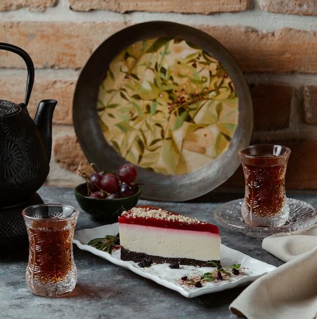 Uma deliciosa fatia de cheesecake de nova york com geléia de morango na parte superior e chocolates na base Foto gratuita