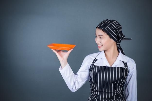 Uma dona de casa segurando um prato vazio com comida Foto gratuita