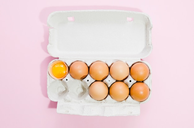 Uma dúzia de ovos com fundo de cor Foto gratuita
