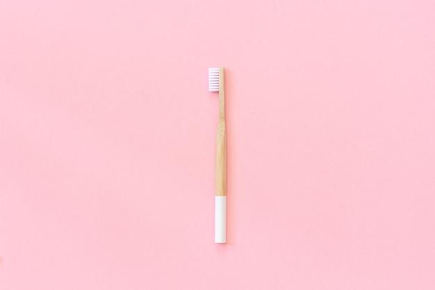 Uma escova de bambu eco-friendly natural com cerdas brancas em papel rosa. zero conceito de desperdício. Foto Premium
