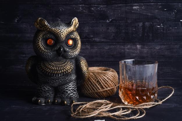 Uma estatueta de coruja, uma bola de linha e um copo de uísque. composição de um feriado caro Foto Premium