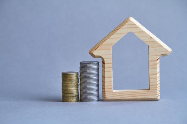 Uma estatueta de madeira da casa com duas colunas de moedas nas proximidades em fundo cinza, o conceito de comprar ou alugar um edifício, foco seletivo Foto Premium