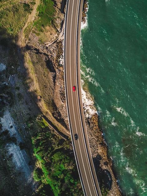 Uma estrada estreita e curvilínea com carros ao lado de montanhas verdes Foto gratuita