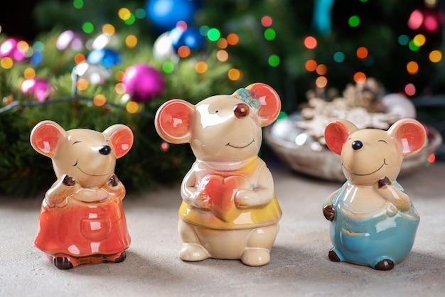 Uma família de estatuetas de cerâmica de ratos em uma luzes de natal. Foto Premium