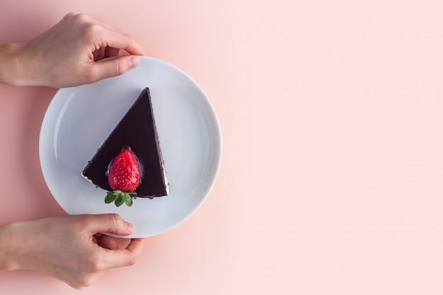 Uma fatia de bolo doce de morango com gotas de cobertura de chocolate em um prato branco nas mãos de rosa Foto Premium