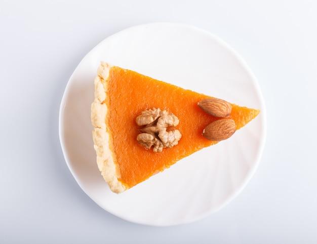 Uma fatia de torta de abóbora doce americana tradicional isolada na superfície branca. Foto Premium
