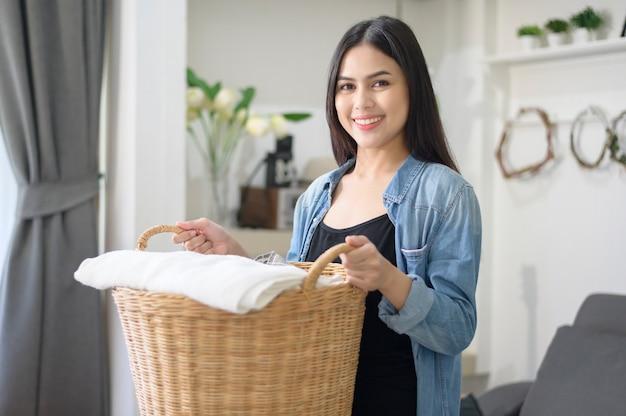 Uma feliz dona de casa está carregando panos de balde para lavar na casa. Foto Premium