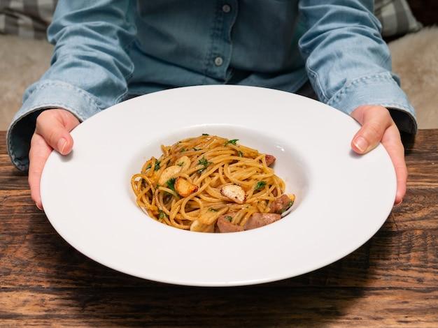 Uma fêmea usa as mãos para segurar e entregar um prato de espaguete picante com lingüiça de porco e alho em tigela branca, cozinha italiana Foto Premium