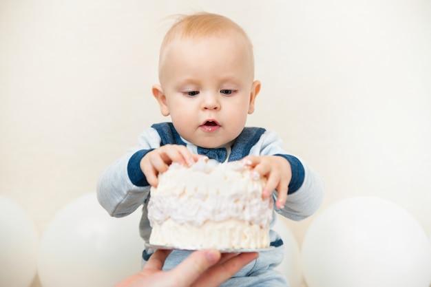 Uma festa de aniversário de bebê ano. bebê comendo bolo de aniversário close-up Foto Premium