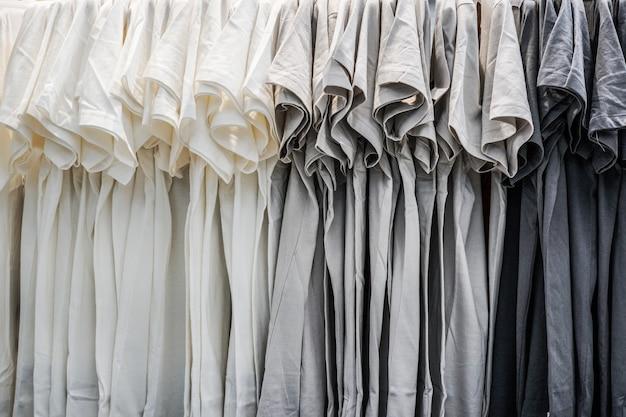Uma fileira de camiseta pendurada na prateleira Foto Premium