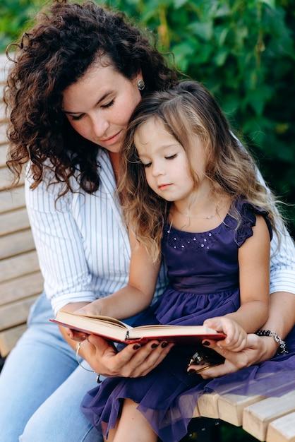 Uma filha e sua mãe estão sentadas em um banco no parque, lendo um livro interessante Foto Premium