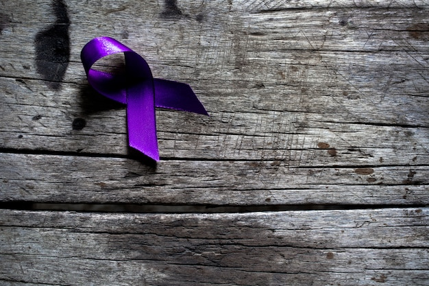 Uma fita roxa sobre uma superfície de madeira rústica cinza escura, violência contra o conceito de mulheres Foto Premium