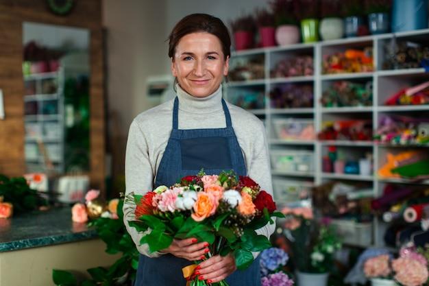 Uma florista de mulher bem-humorada fica no meio de uma loja de flores com um buquê de lindas flores Foto Premium
