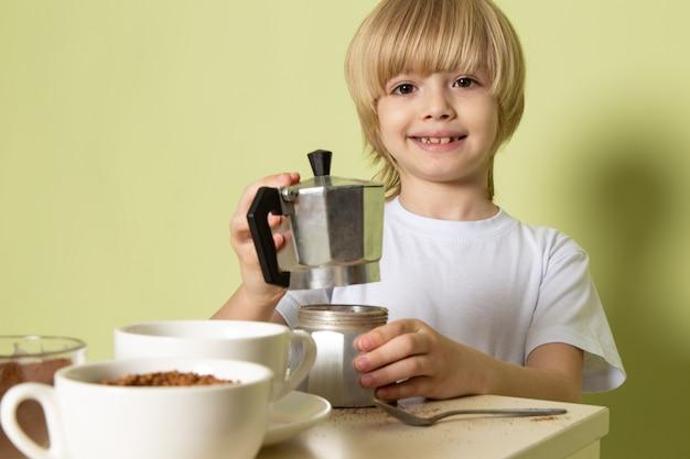 Uma fonte ver menino sorridente feliz preparando café beber em cima da mesa no chão de pedra colorida Foto gratuita