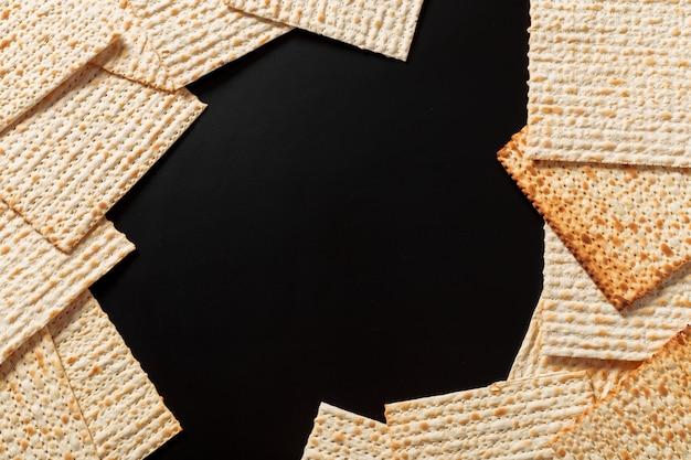 Uma foto do matzah ou do matza remenda no fundo preto. matzah para as férias da páscoa judaica. copyspace Foto Premium