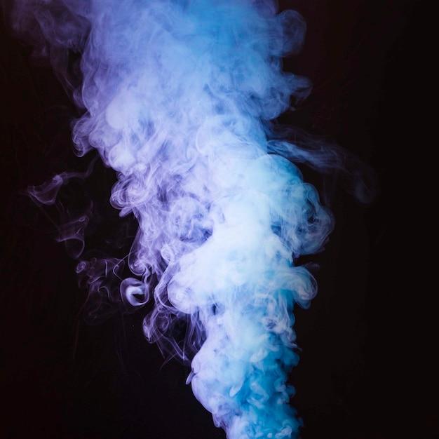 Uma fumaça espessa girando na frente de fundo preto Foto gratuita