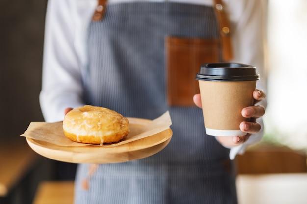 Uma garçonete segurando e servindo um pedaço de rosquinha caseira na bandeja de madeira e uma xícara de café Foto Premium