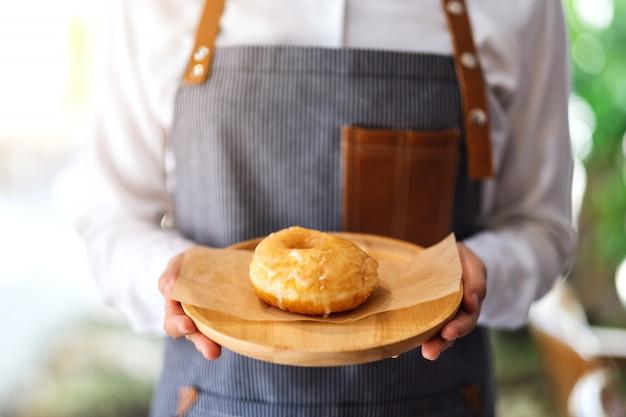 Uma garçonete segurando e servindo um pedaço de rosquinha caseira na bandeja de madeira Foto Premium