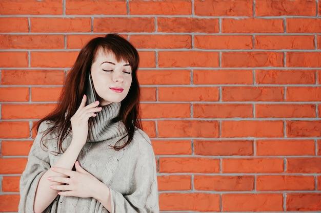 Uma garota bonita falando pelo celular, olhos fechados, sonhadoramente sorrindo Foto Premium