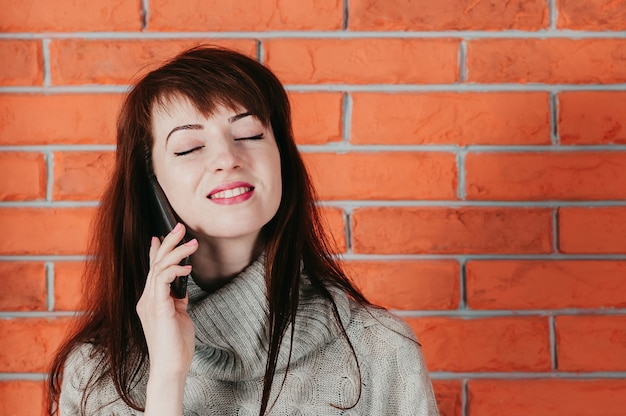 Uma garota bonita falando pelo celular, sorrindo, olhos fechados, com parede de tijolos no fundo Foto Premium