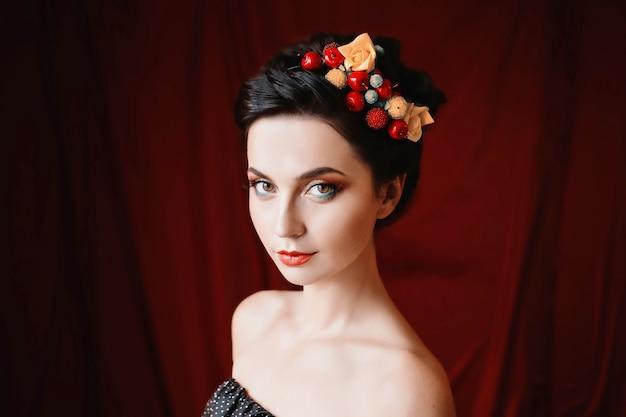 Uma garota bonita, morena com olhos castanhos com maquiagem brilhante, maquiagem com bagas e flores no cabelo, lábios vermelhos, aparência incomum, uma mulher com pele bronzeada em fundo escuro vermelho Foto Premium