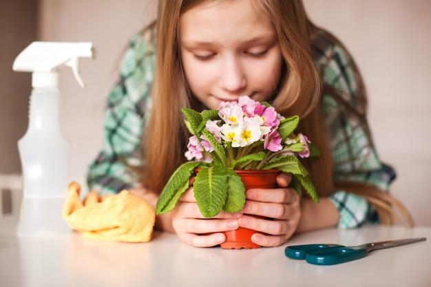 Uma garota cheira uma flor e cuida de plantas em sua casa, close-up Foto Premium