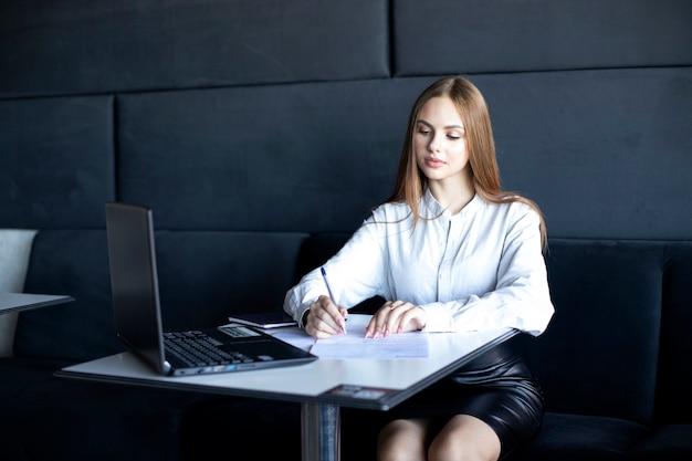 Uma garota com cabelo comprido em uma camisa branca preenche documentos Foto Premium